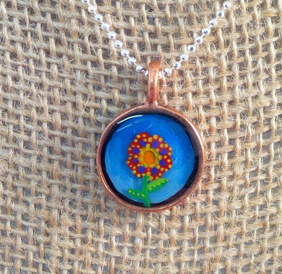 Hand painted resin pendant in a round copper bezel