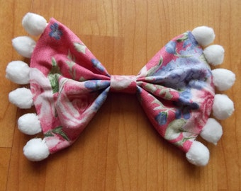 Pink floral bow with pompoms.