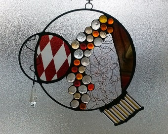 A contemporary and unique stained glass panel made  with a variety of techniques.  Is it an undersea creature?  From another planet?