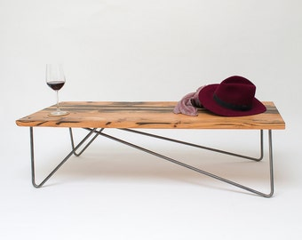 Reclaimed wood beam coffee table with asymmetrical steel hairpin legs