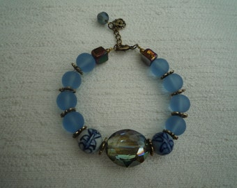 Pretty blue beaded bracelet with antique brass separator 'flowers' and adjustable lobster clasp.