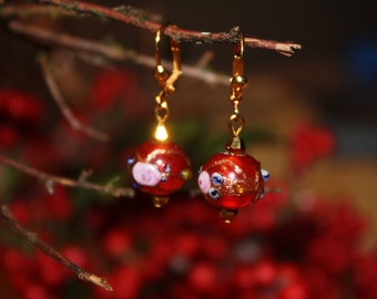 Red lampwork earrings with gold and pink floral beads.