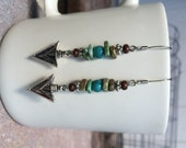 Earthy bohemian arrowhead earrings with green stone chip beads, turquoise beads, silver beads, wooden beads, and silver arrowhead charm