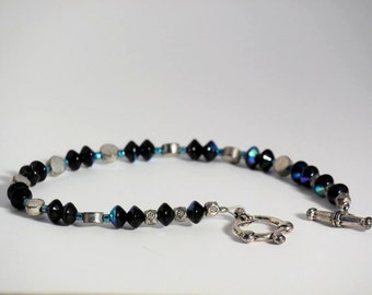 Bracelet made of AB finished black saucers and silver plated metal beads with a toggle clasp.