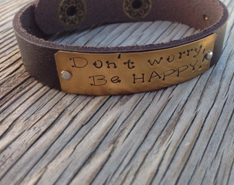 A riveted, a 1/2 inch wide brown leather cuff bracelet hand stamped with don't worry, be happy