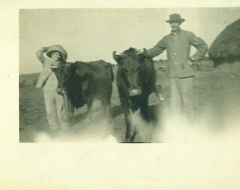 Happy Farmer and Wife Standing With Cows Farm Field Fun Hats RPPC Real Photo Postcard Vintage Antique Black White Photo Photograph