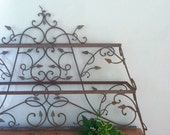 Vintage iron shelving rack with decorative vine and leaf detail
