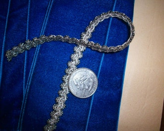 """1 yard 2 1/2"""" of a narrow metal antique silver with black threads trim"""