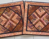 A pair of handcrafted quilted batik pillow covers in shades of peach and rust with navy accents
