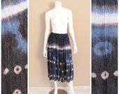 Vintage India gauze cotton tie dye skirt with silver thread, and brass beads 1980s. Blue tie dyed with gold print.