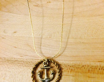 Gold tone anchor necklace with white gem