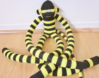 Yellow and black striped knee sock monkey with extra long legs