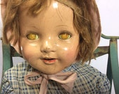 Large creepy composition doll with crackled yellow sleepy eyes