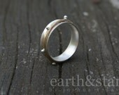 silver fidget ring with studded golden spinner