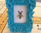 Completed Bee Cross-stitch in ornate blue frame