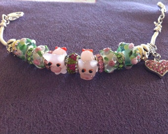Pink piggies, beautiful pastel green and pink lampwork beads, crystal rondelles and heart, and metal pigs.