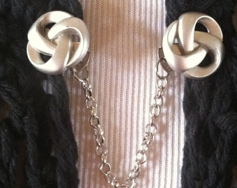 The mattie  brushed silver tone knot sweater clip is the modern way to wear an old favorite.