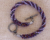 Kumihimo bracelet in multi-purple color seed beads.