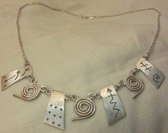 Sterling silver, symbol and swirl necklace