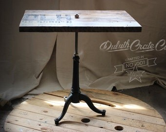 Vintage industrial side table. Cast iron base with reclaimed grain elevator wood top.