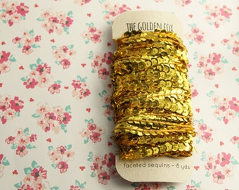 threaded gold faceted sequins [8 yds]