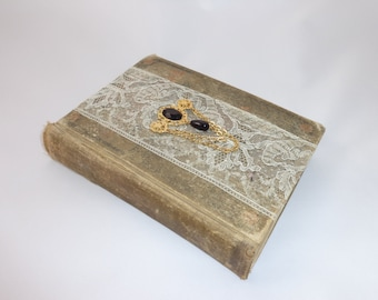 Beautiful vintage book adorned with vintage lace and vintage jewelry
