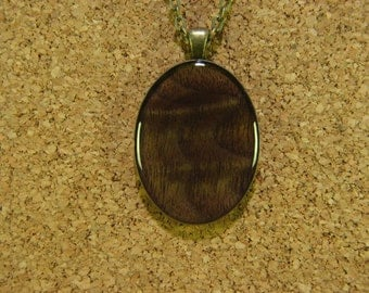 Figured Black Walnut wood, resin encased in antique brass finish pendant bezel with chain