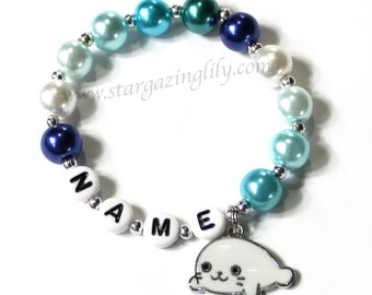 Sweet Seal Pup Charm Bracelet. Pearl charm bracelet w cute enameled baby seal charm. Kids thru Adult Sizes. Blue and White pearl bracelet.