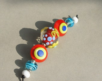 Handmade lampwork glass beadset in vibrant colors like red, blue, yellow and green by Flamejewels.