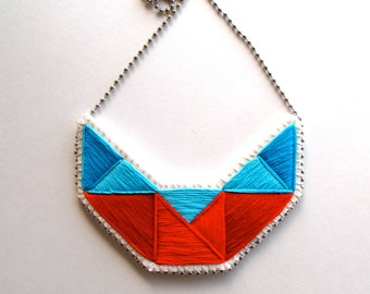 Embroidered geometric statement bib necklace in reds and blues on cream muslin with felt backing on silver ball chain