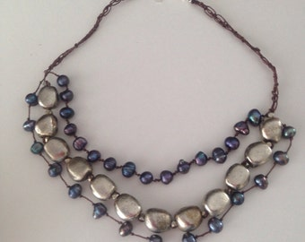 "Beaded choker. ""Hues of Blues"" is three tiers of freshwater pearlsl and heavy metal pebble beads hand strung and knotted on silk. 16"" long."