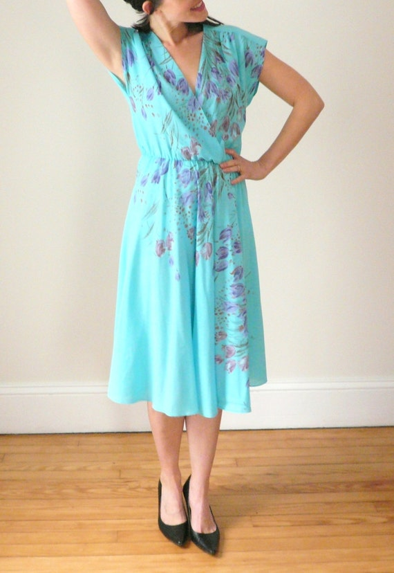 Comfy La Cera dress of soft % cotton comes in a floral and paisley print of teal, black, and taupe hues. Features include a v-neckline, 2/3 sleeves, two inseam pockets, and a ruffled flounce hemline.