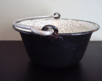 Unique vintage black enamelware pan with metal swing handle and green and white swirl interior