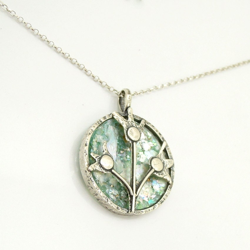 3 silver flowers set in a round pendant with roman glass