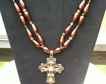 Cross on double strand of brown glass pearl necklace