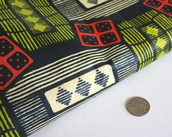 Yardage of polished cotton fabric with ethnic African pattern. Tribal inspired, retro, geometric, graphic, chartreuse, orange, black.