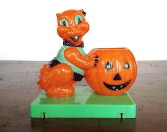 Vintage E. Rosen or Tico cat pushing jack o' lantern pumpkin, platform, 1950s hard plastic styrene Halloween candy container, orange, green