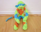 Neon argyle sock monkey plush doll - lime green, electric blue, and orange with vintage button