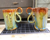 Pair of Red, brown, green, and blue mugs