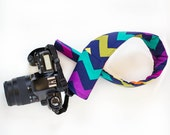 DSLR camera strap cover with lens cap pocket.  multi colored chevron.