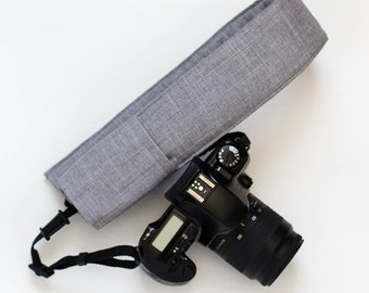DSLR camera strap cover with lens cap pocket.  simply grey.