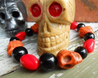 The Real Dia de Los Muertos skull stretch bracelet in orange, red and black