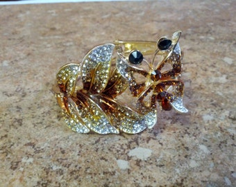 Lovely and ornate Butterfly bracelet in gold tone metal with clear, brown,black and yellow rhinestones
