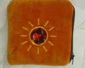 A coin purse in orange velvet with a sun on the front