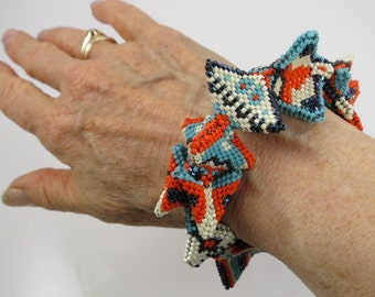Primitive beaded cuff with horns in blue, black, orange and ivory
