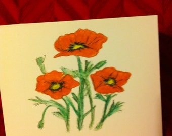 Trio of red poppies printed on greeting card.