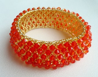 Golden bracelet of beads and red crystals