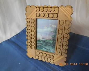Picture frame made of cross cuts of wood, with seascape picture.
