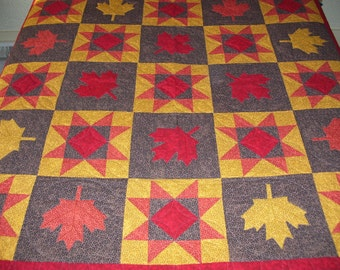 This is a large quilt would be good for a lap or table. It is handquilted in the traditional fall colors. The leaves are appliqued on.