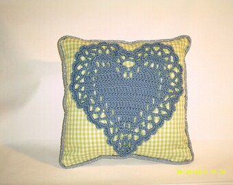 lime green  gingham pillow with a blue crocheted heart sewn on it.